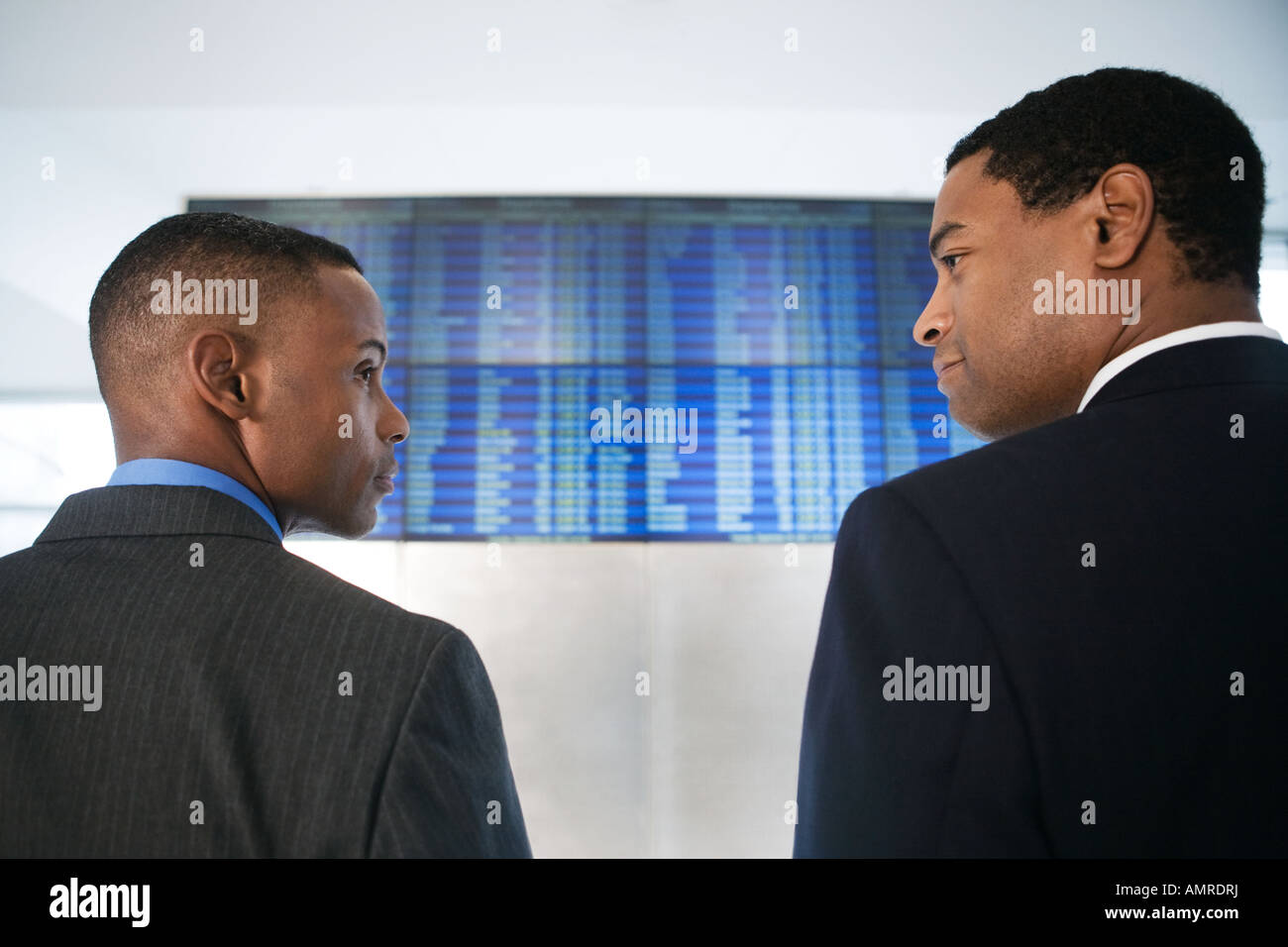 African businessmen in front of Arrival Departure board - Stock Image