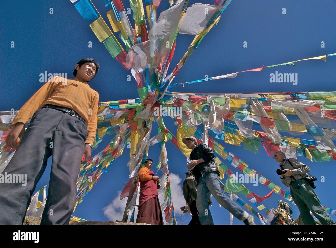 Standing under prayerflags TIBET A young man in western dress a monk and a western photographer Tibet Stock Photo