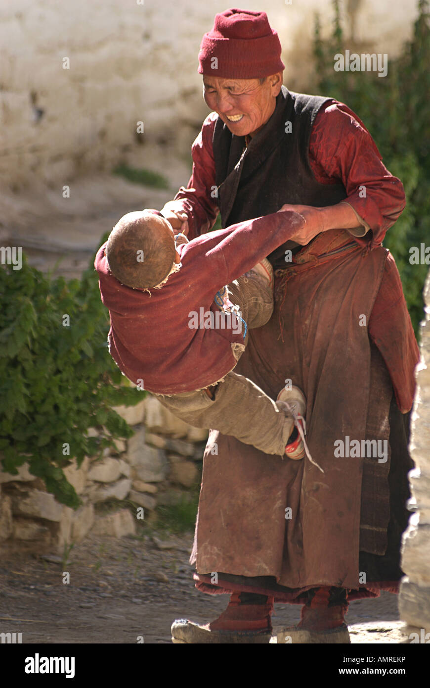 Tibetan woman playing with her energetic grandson at Rongbuk Monastery Tibet Stock Photo