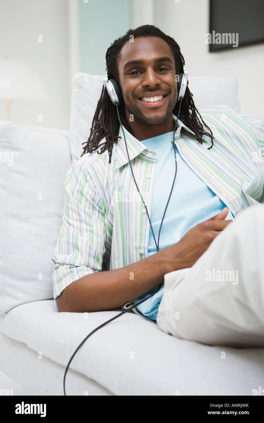 African man listening to headphones - Stock Image