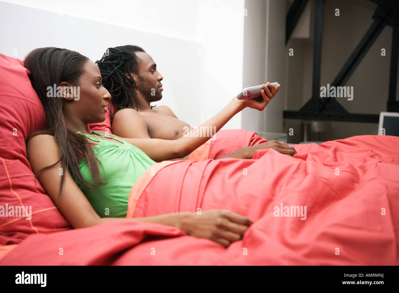 African couple watching television in bed - Stock Image