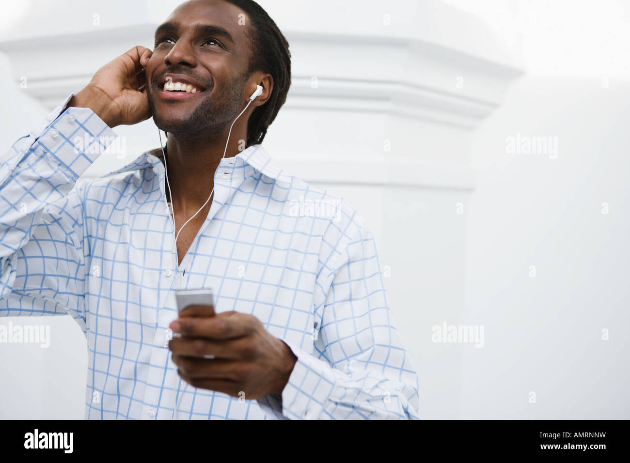 African man listening to mp3 player - Stock Image