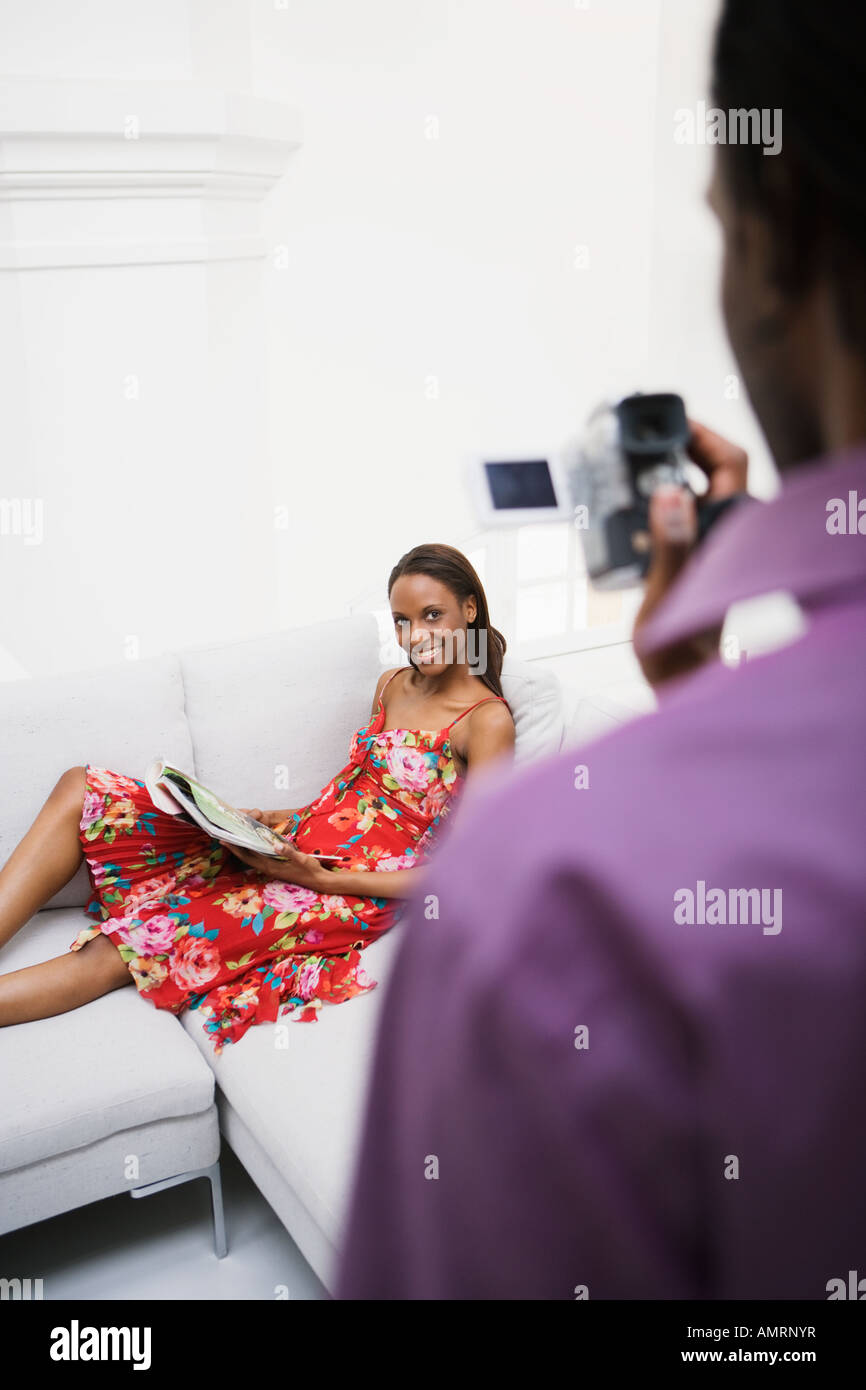 African man video recording girlfriend - Stock Image