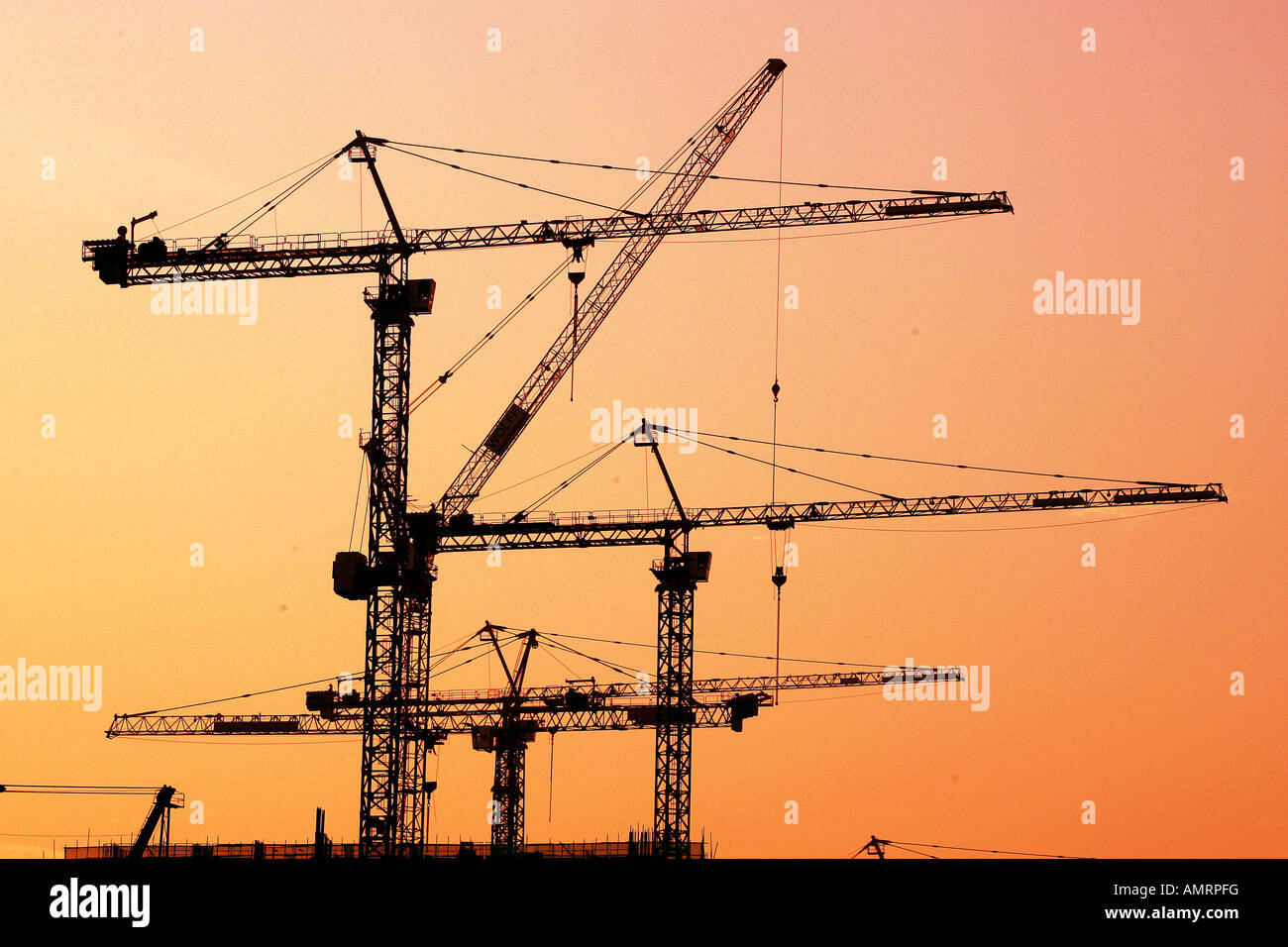 High cranes and construction building work in the sunset over Macau - Stock Image