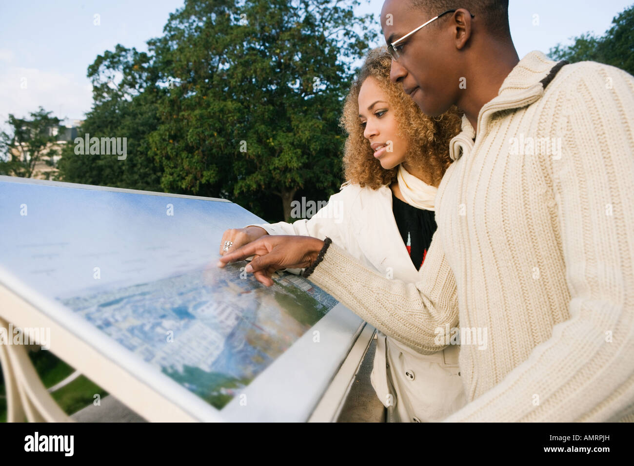 African couple looking at tourist information board - Stock Image