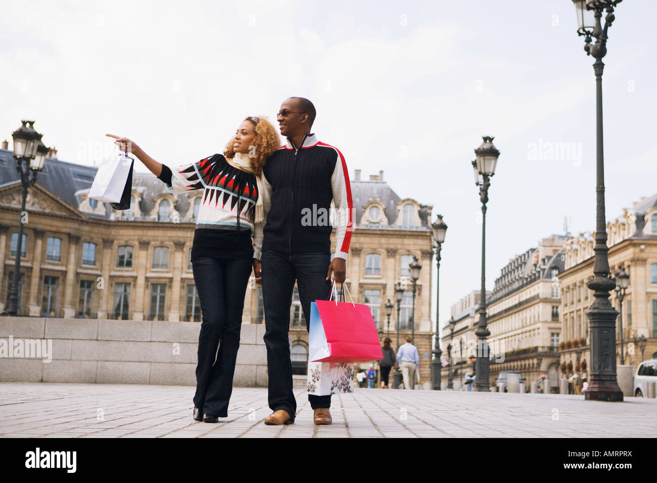 African couple carrying shopping bags - Stock Image