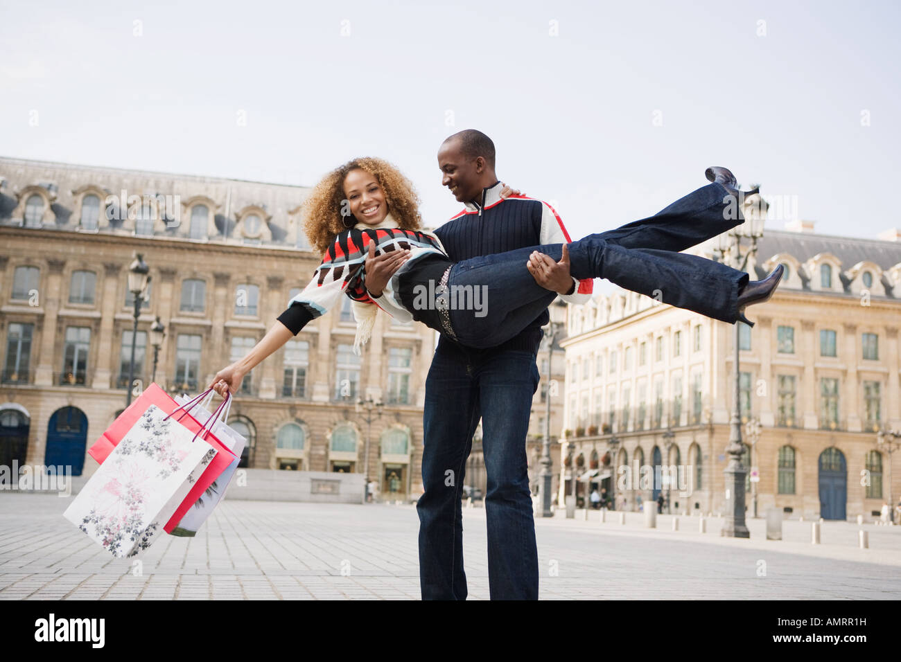 African man carrying girlfriend - Stock Image