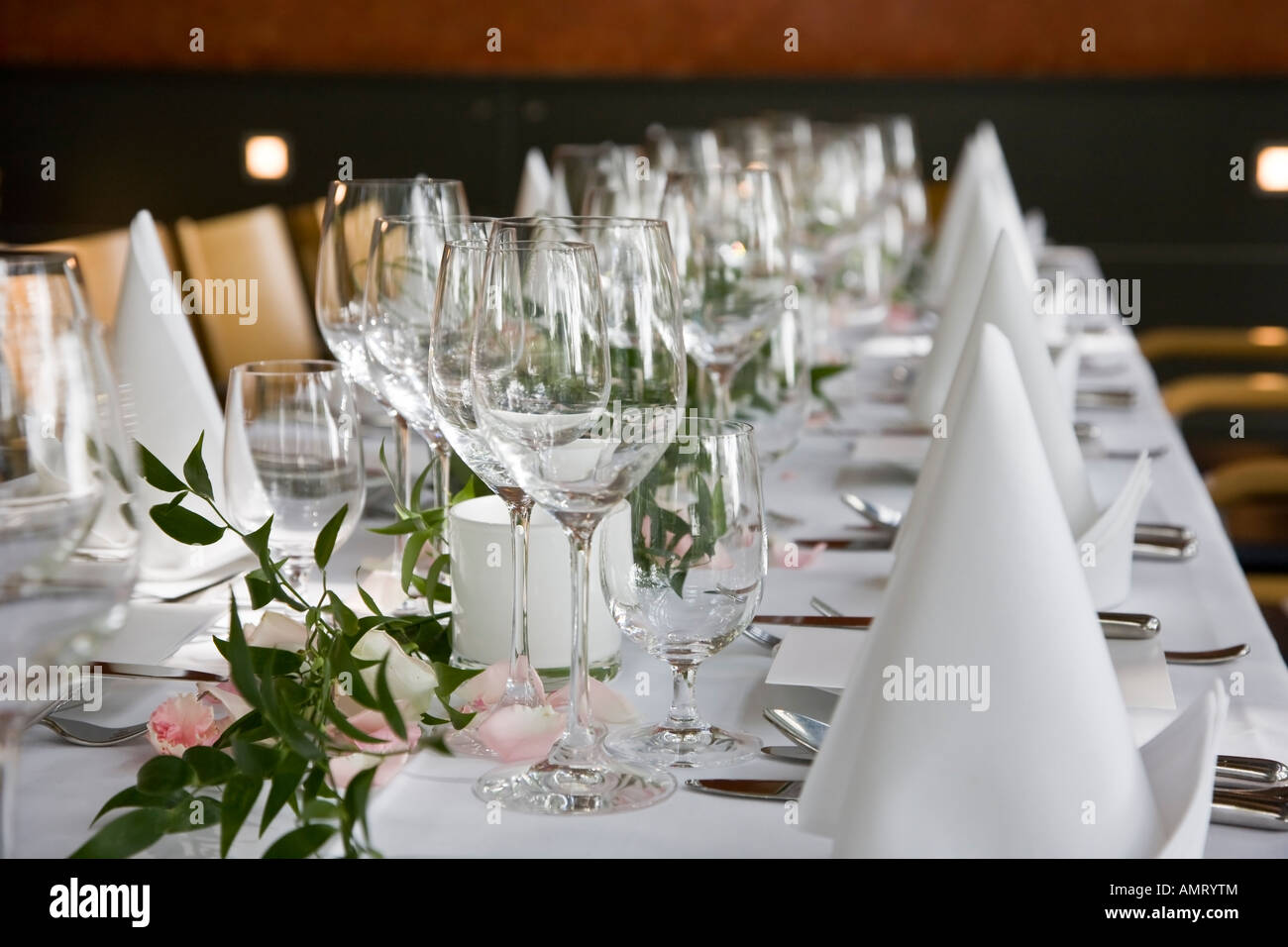 Well-laid table with white folded serviettes and wine glasses. - Stock Image