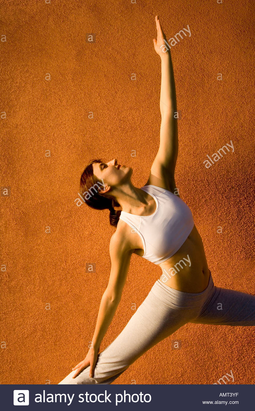 Woman in yoga stretch looking toward the sky, strength beauty balance and  grace, southwestern style Terra-cotta  colored wall - Stock Image