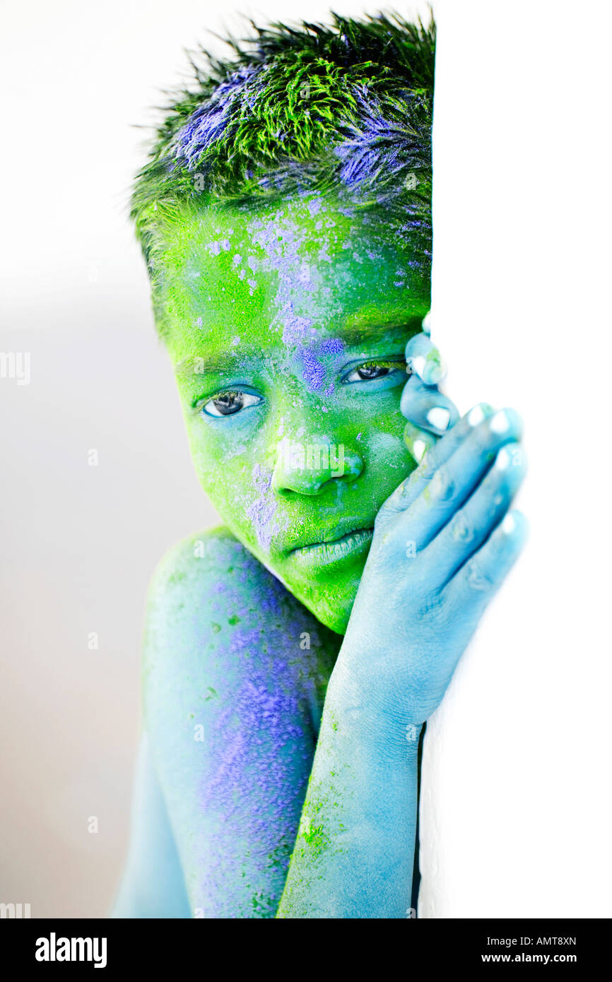 Young Indian boy covered in coloured powder pigment Stock Photo