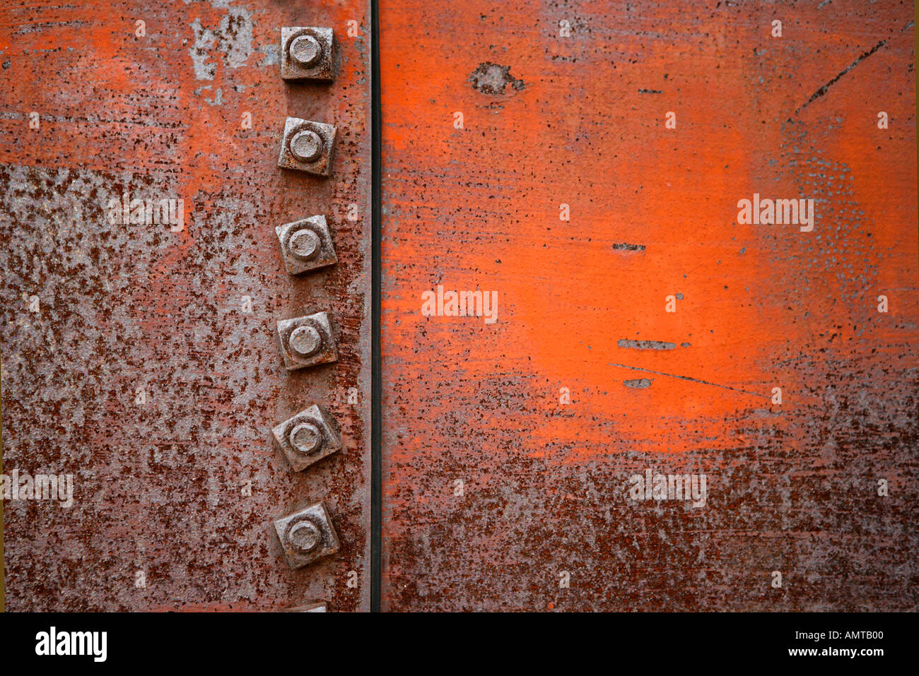 A close up of a seam on an old water tank showing the rust and fastening nuts - Stock Image