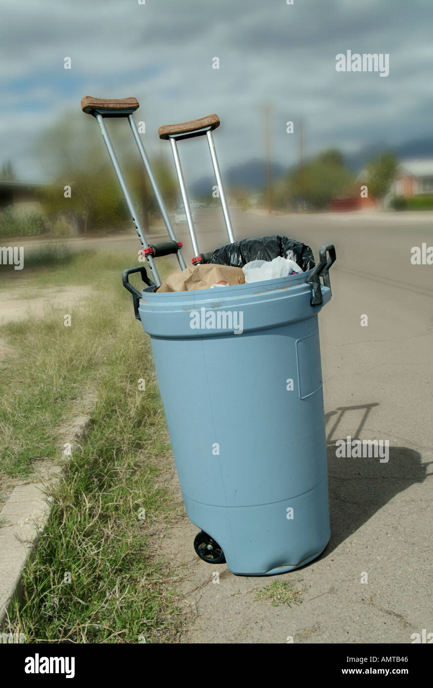 Crutches that are no longer needed in a trash can by the side of the road - Stock Image
