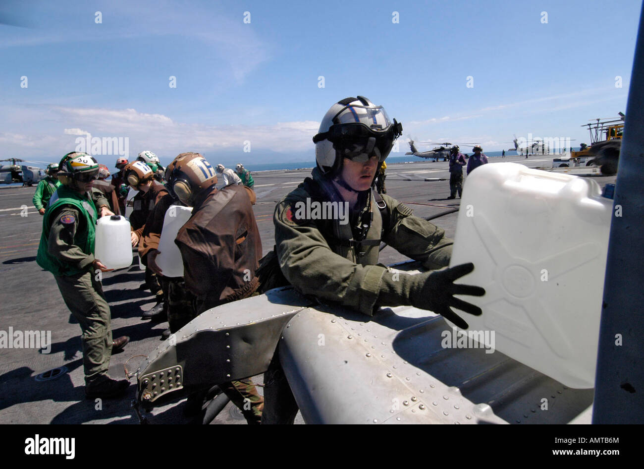 Crewman load water and relief supplies onto a helecopter on the USS Abraham Lincoln of shore of the Tsunami torn - Stock Image