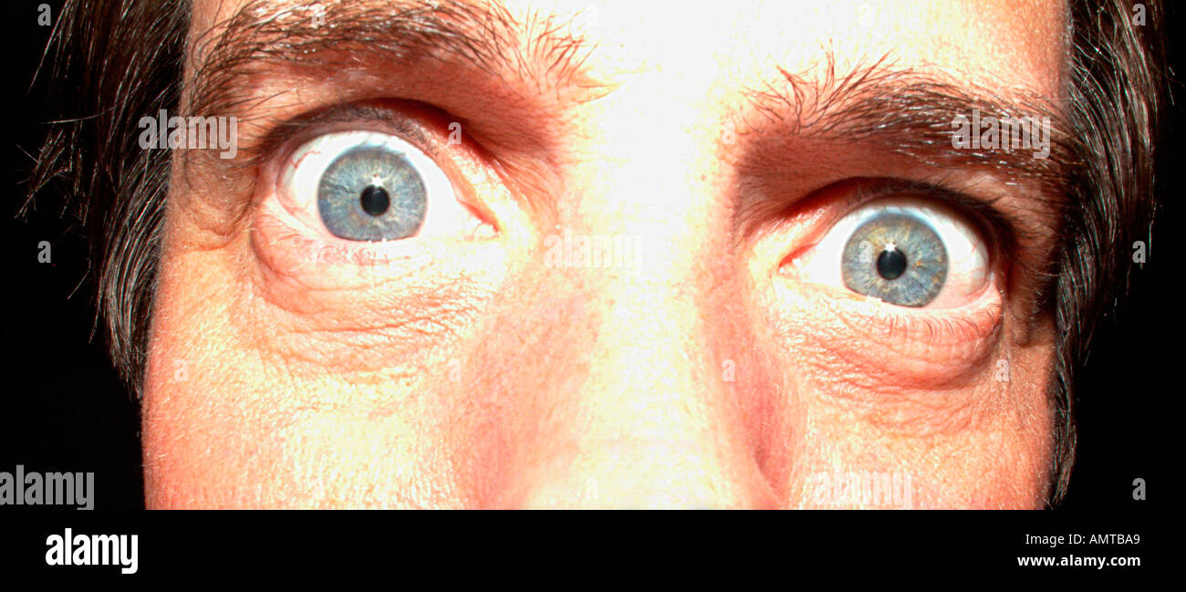A mans eyes wide open in mock surprise or shock - Stock Image