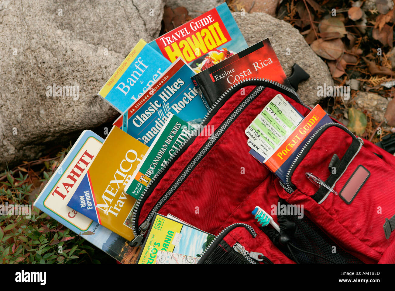 A hiker's backpack overflowing with travel books guides and maps - Stock Image