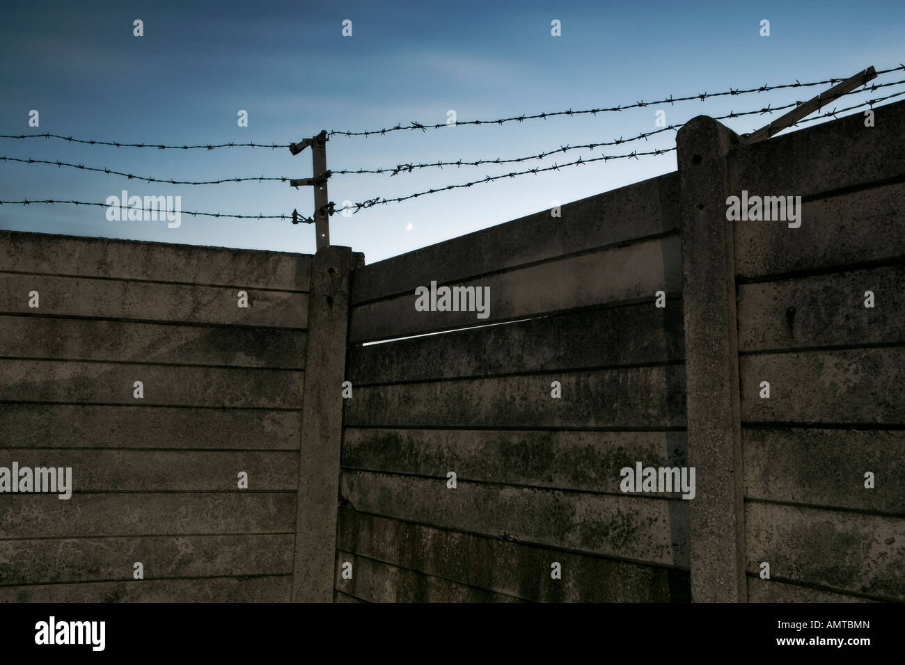 Prison-style high concrete slab wall with barbed wire fenced area above - Stock Image