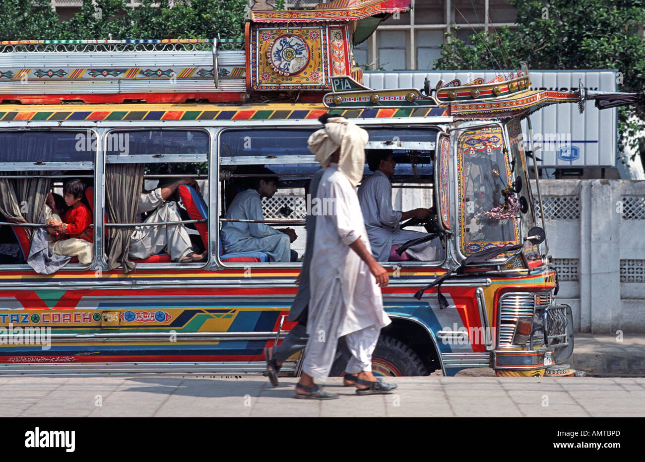 Urban street scene Pakistan Pedestriansbeing passedby a local bus on the streets of Peshawar Pakistan - Stock Image