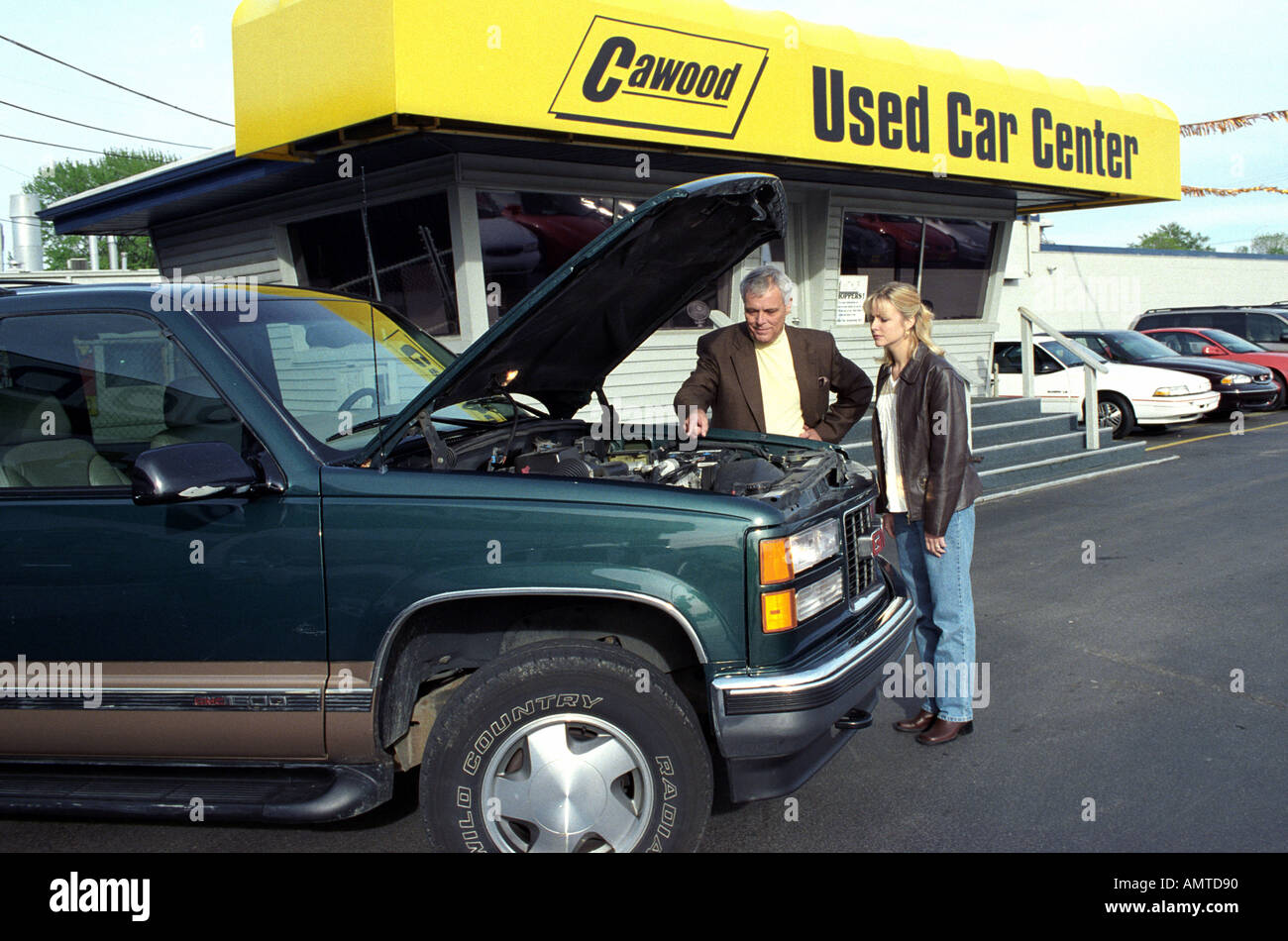 College age female shops for a used automobile and looks at