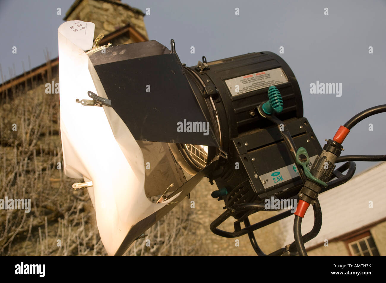 Large 2.5kw film lantern light with scrim clipped to the barn doors to diffuse the light on an outdoor  film location - Stock Image