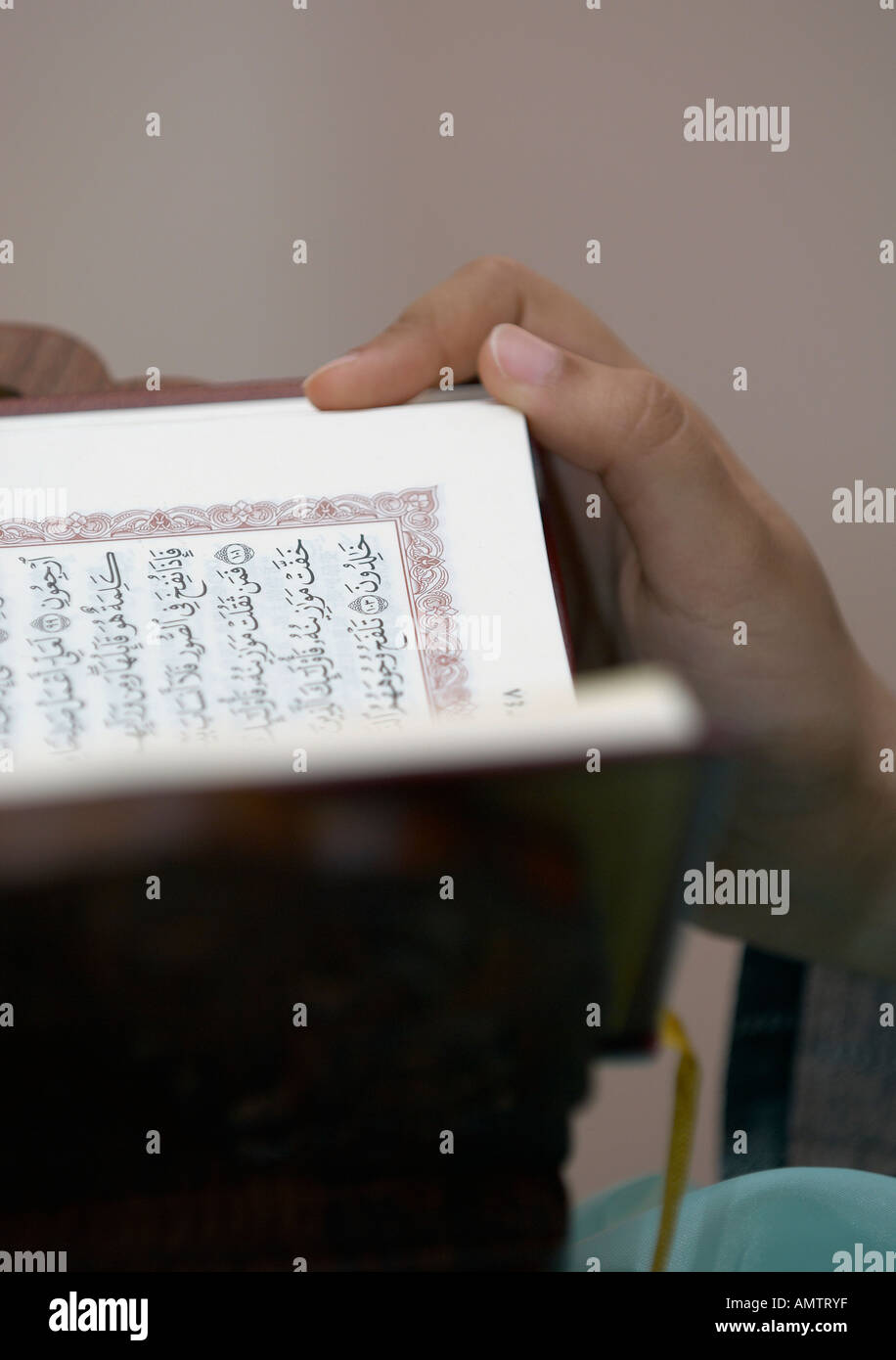 A man's hand on an open copy of the Quran - Stock Image