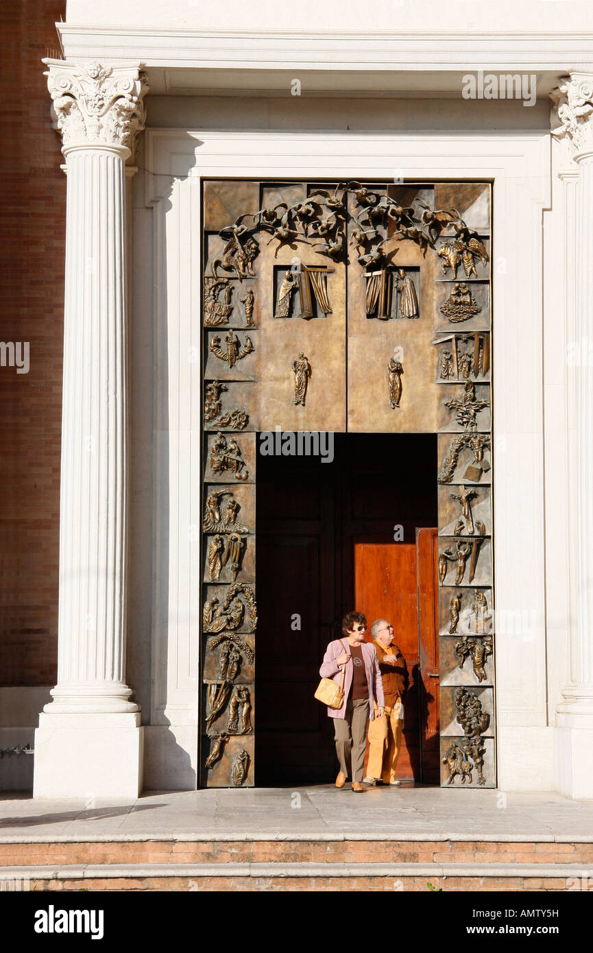Tourists leaving  Jesi Cathedral through the heavy bronze doors..Le Marche Italy - Stock Image