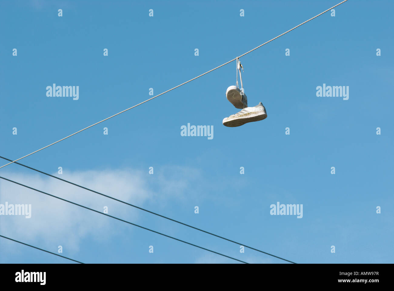 A pair of white sneakers hanging from overhead power lines after being thrown there as a teenage prank - Stock Image