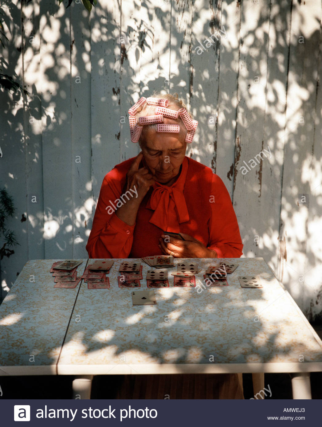 elderly woman plying cards outside - Stock Image