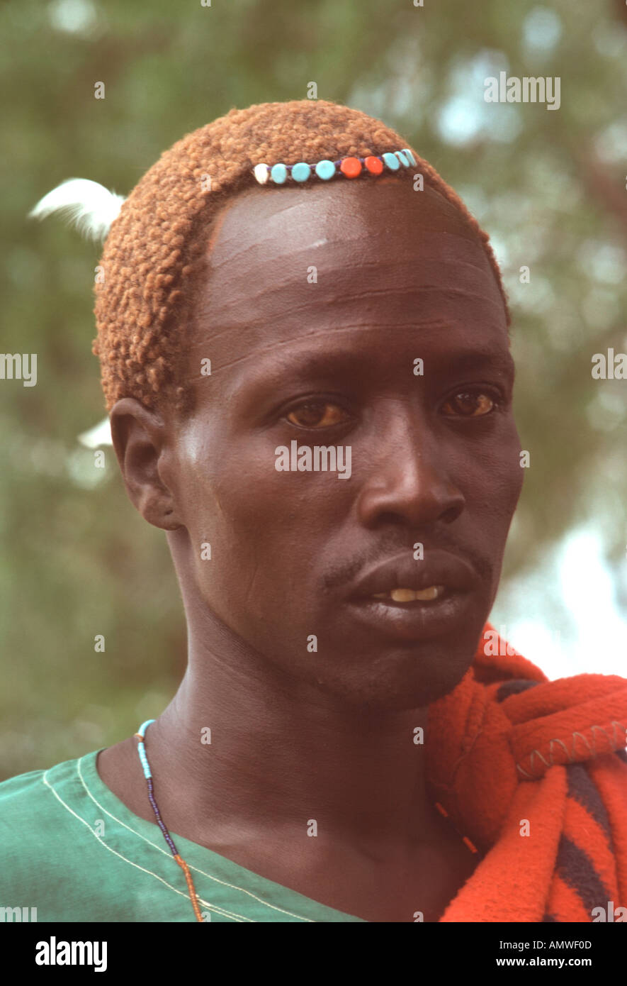 A young Dinka man with tribal scars on his forehead has a neat hairdo simply adorned with beads - Stock Image