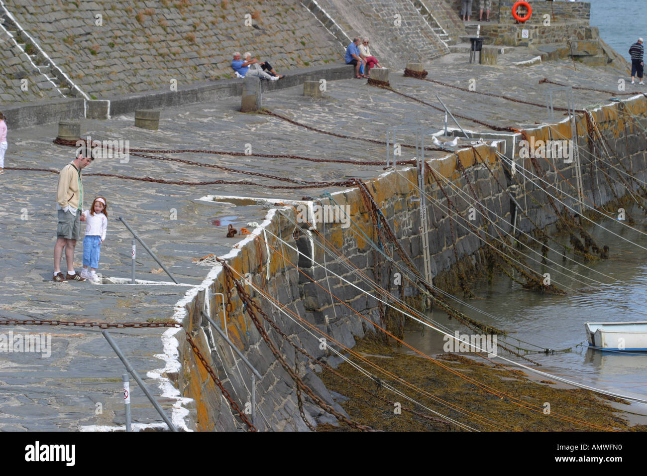 New Quay tourists on harbour wall looking at fishing boats Ceredigion Wales - Stock Image