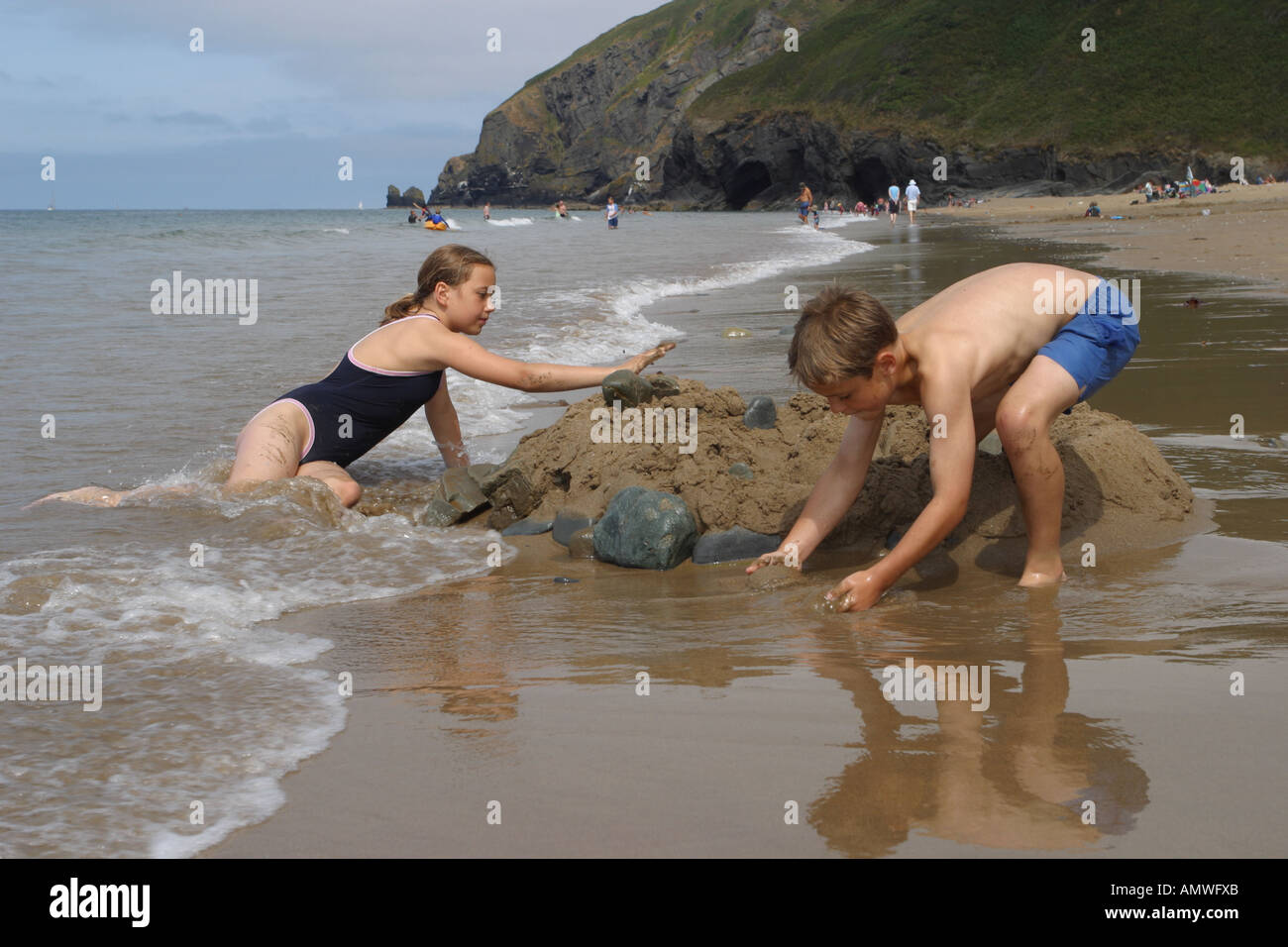 Children playing on the beach at Penbryn Ceredigion Wales building a sand castle near Llangranog - Stock Image