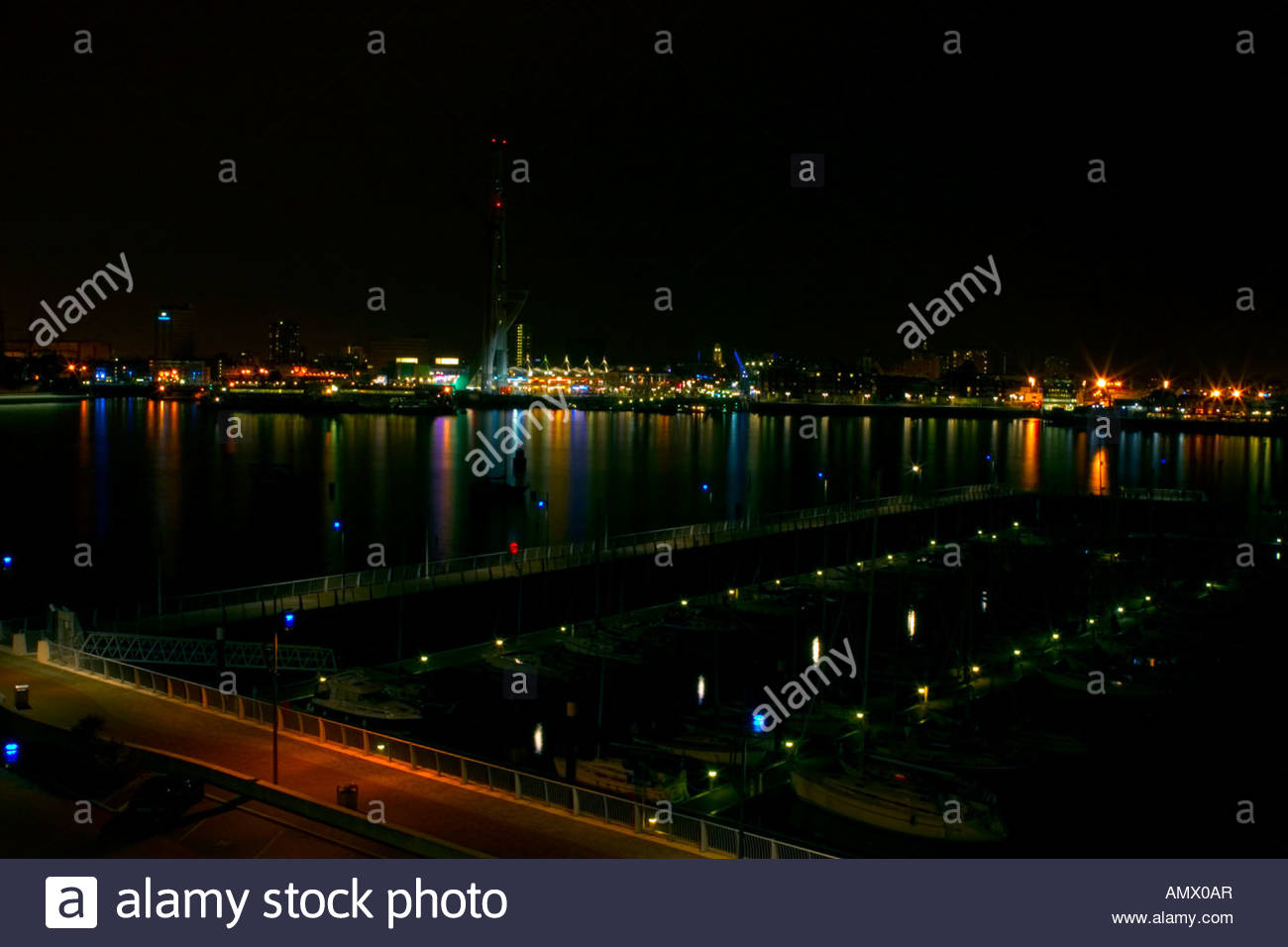 Looking at the water and lights across Portsmouth Harbour to Gun Wharf Quays from Gosport Hampshire UK at night, Stock Photo