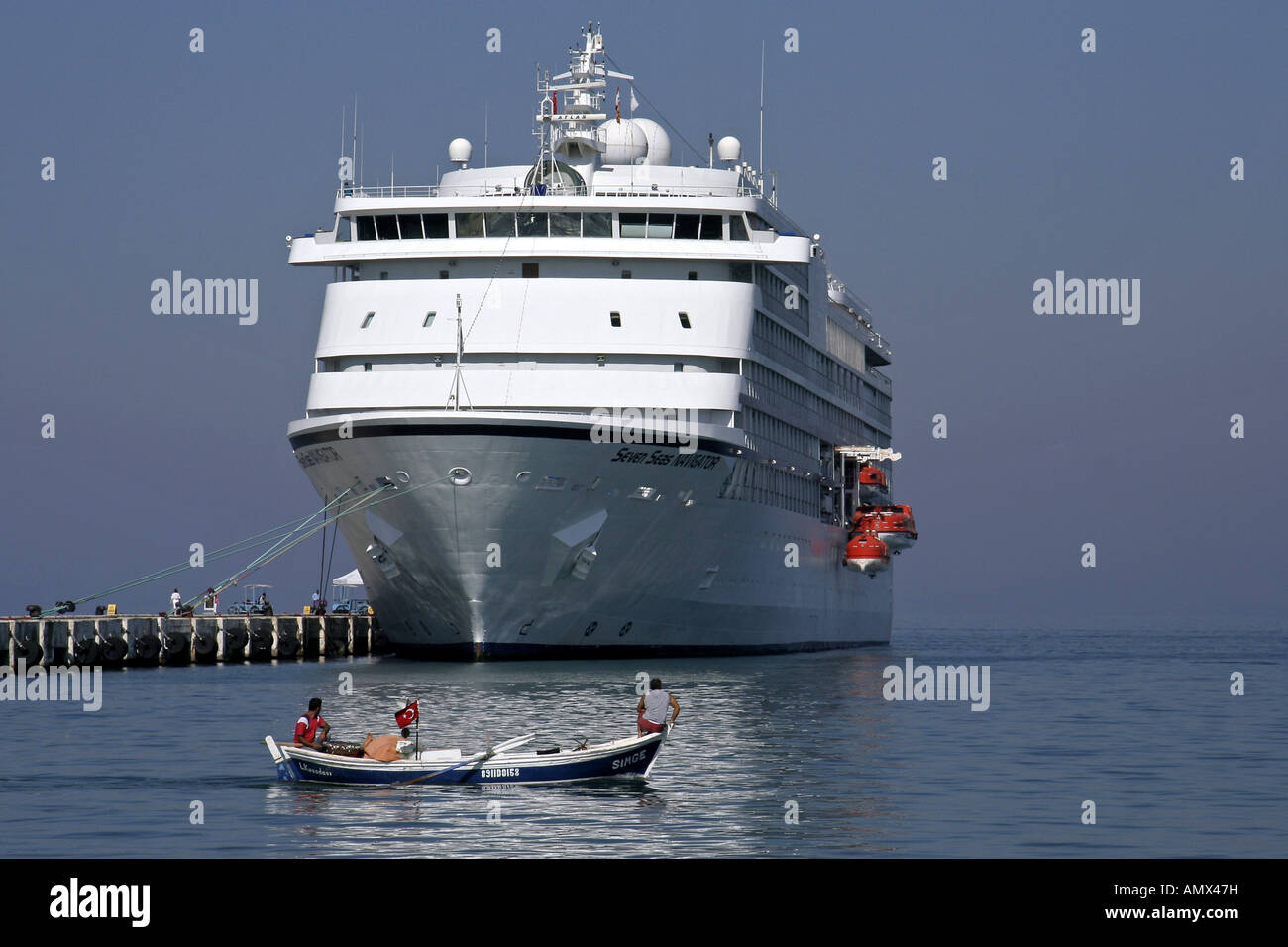 fishing boat in front of cruise liner Seven Seas Navigator, Turkey, Kusadasi - Stock Image