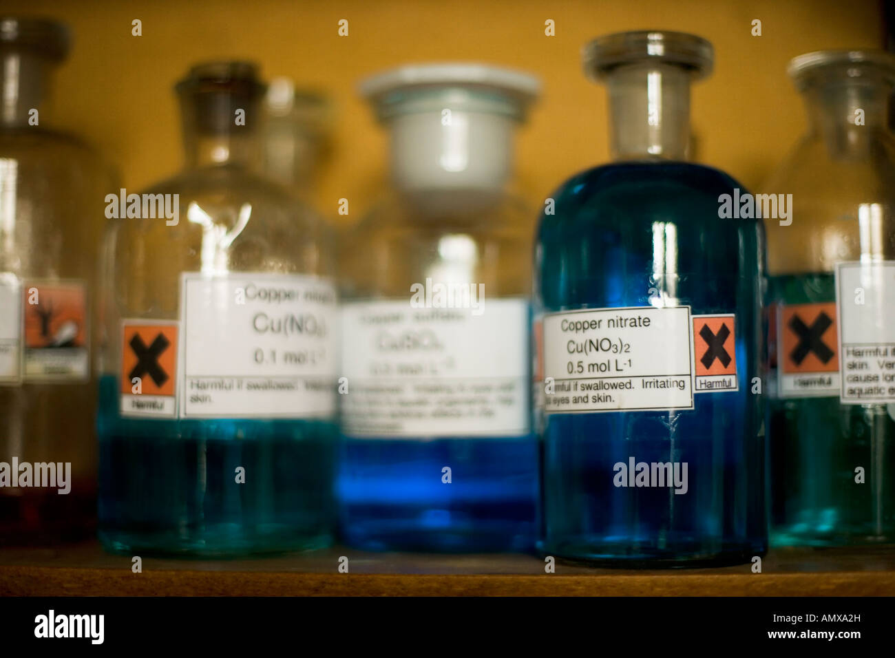 Glass storage jars containing chemicals in a school laboratory - Stock Image
