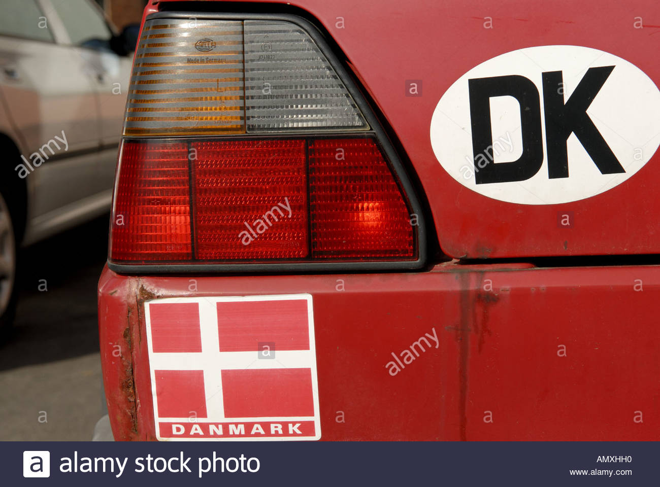 Rear of red car with DK sticker and the Danish flag Copenhagen Denmark - Stock Image