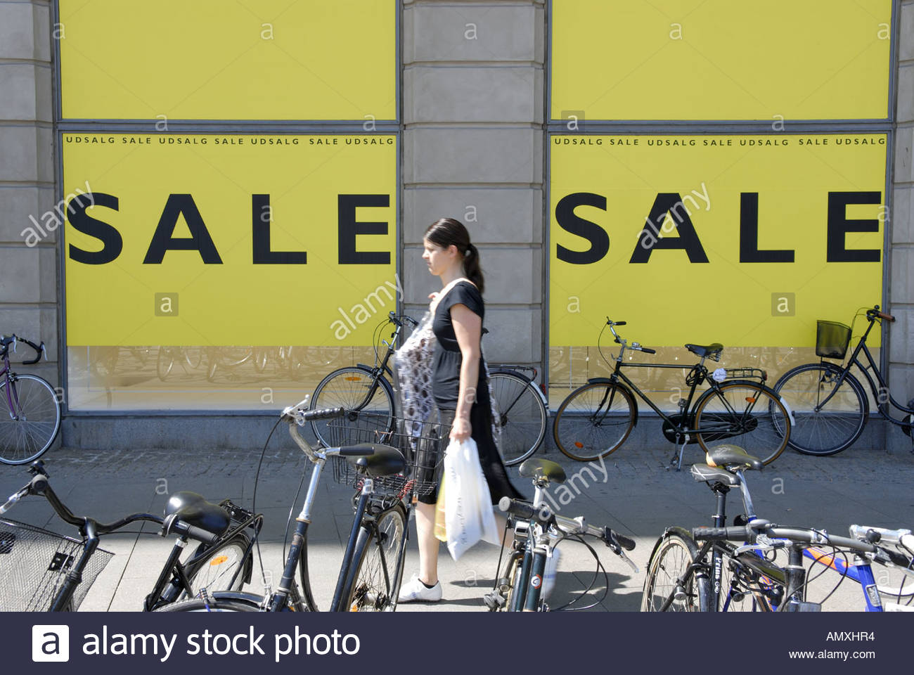 Young woman passing SALE signs of Magasin du Nord Copenhagen Denmark - Stock Image