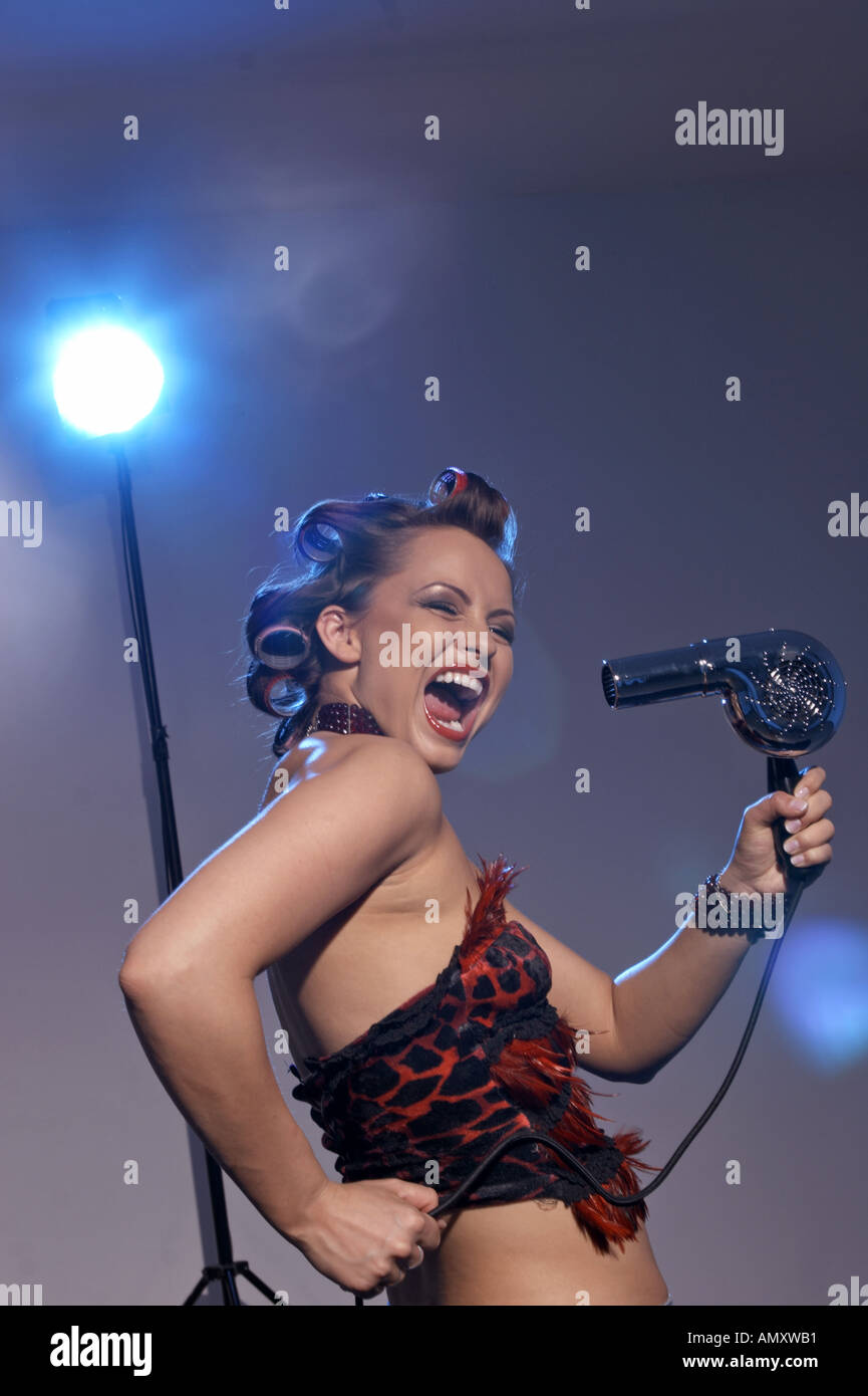 Woman holding hairdrier, singing - Stock Image