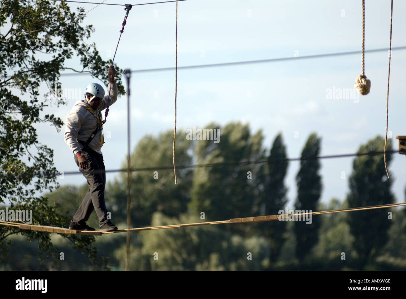 PICTURE CREDIT DOUG BLANE Coloured man crossing a rope brinde on the Aerial Extreme Willen Lake Milton Keynes City of Milton Key - Stock Image