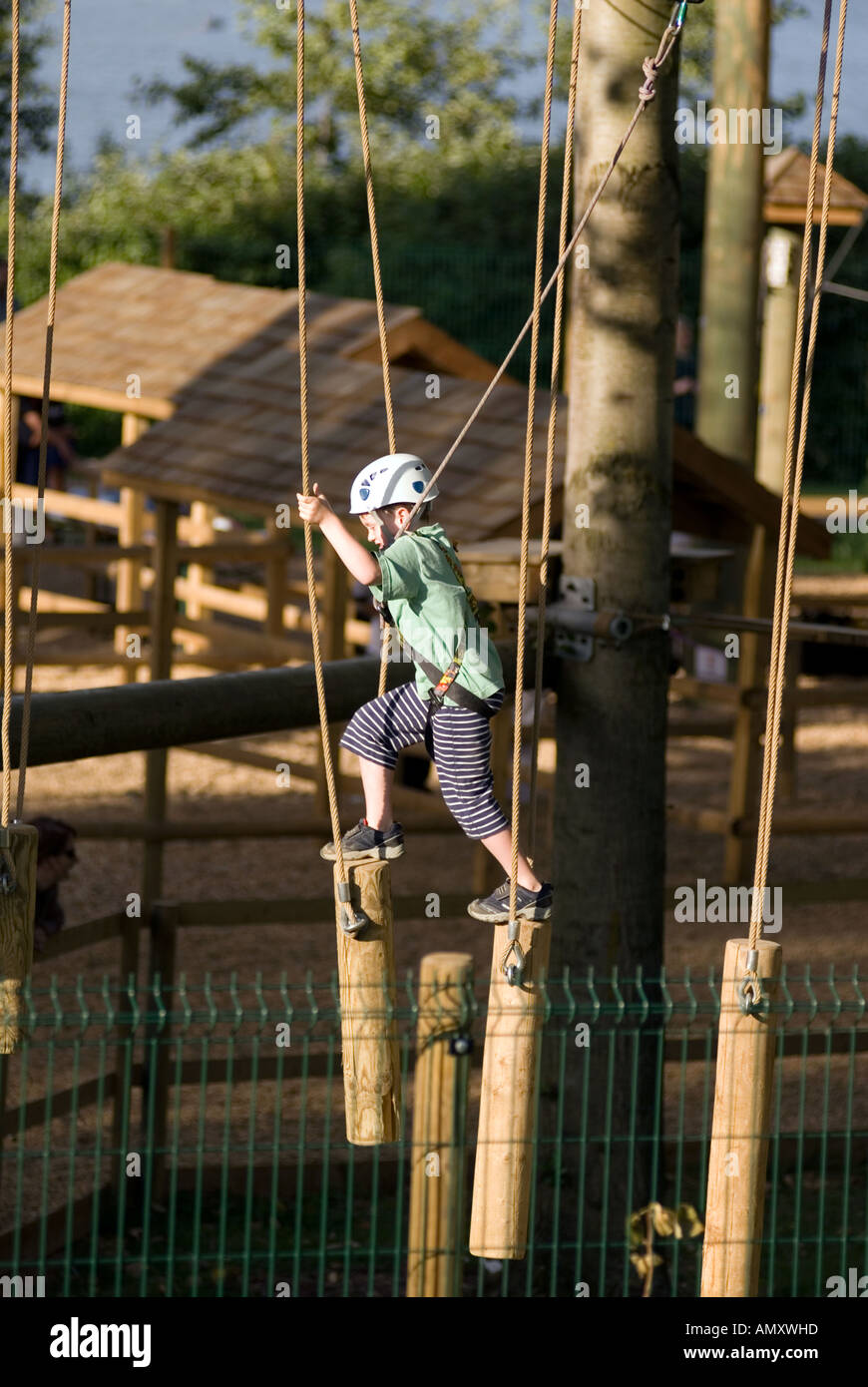 PICTURE CREDIT DOUG BLANE Young boy crossing a log bridge at the Aerial Extreme Willen Lake Milton Keynes City of - Stock Image