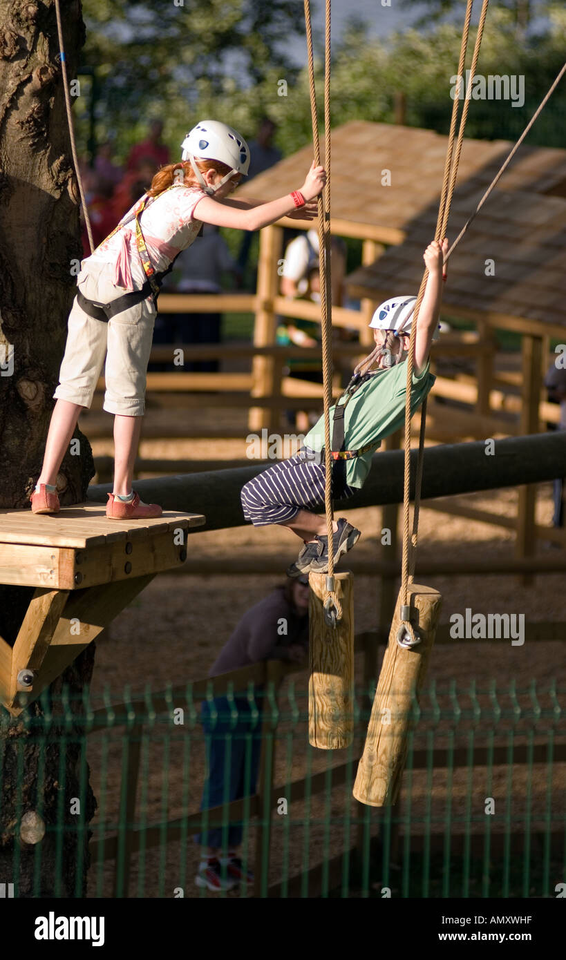 Young girl helping a boy cross a log bright at the Aerial Extreme Willen Lake Milton Keynes City of Milton Keynes Stock Photo
