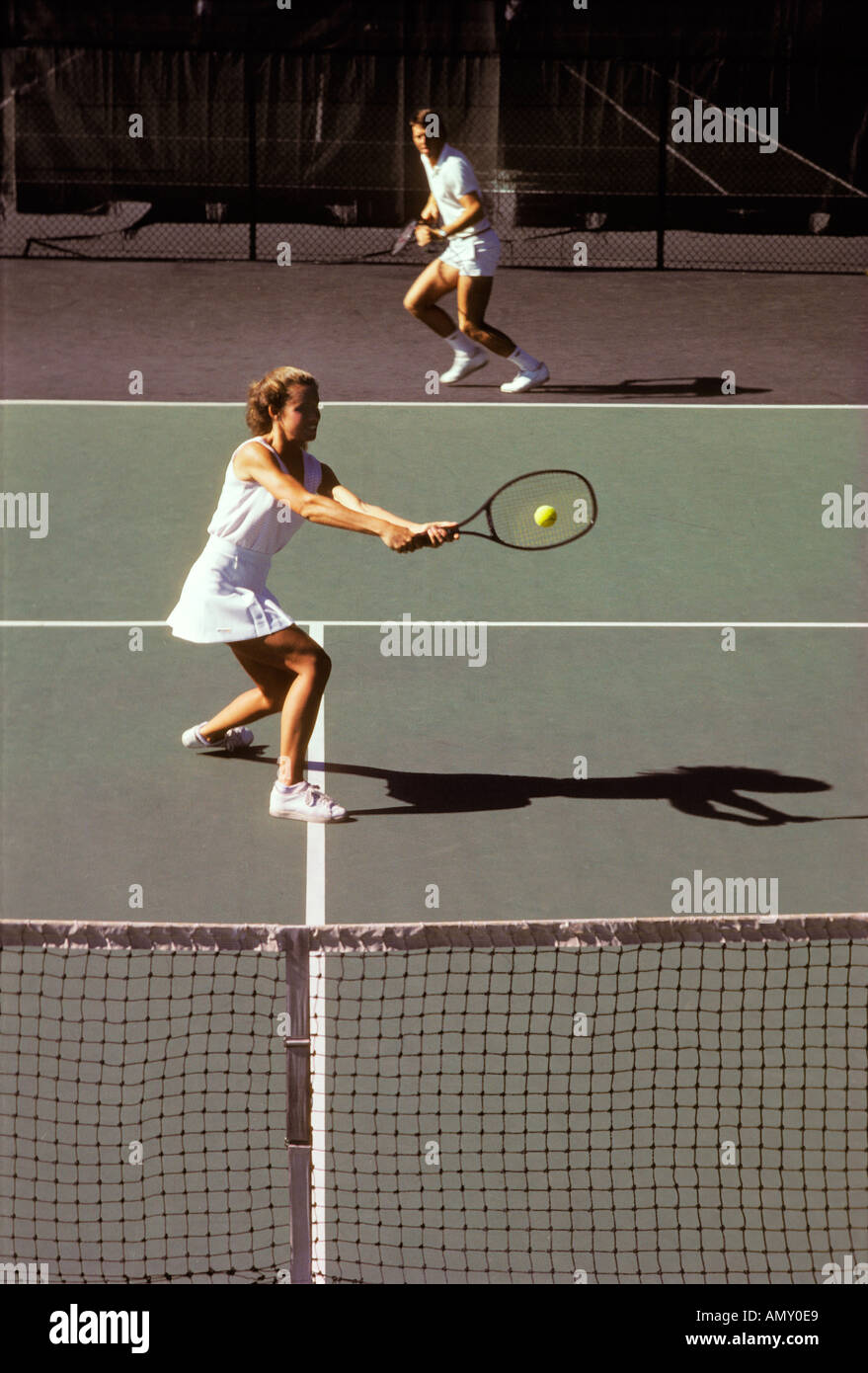 A woman player hits a two handed backhand during a mixed doubles match - Stock Image