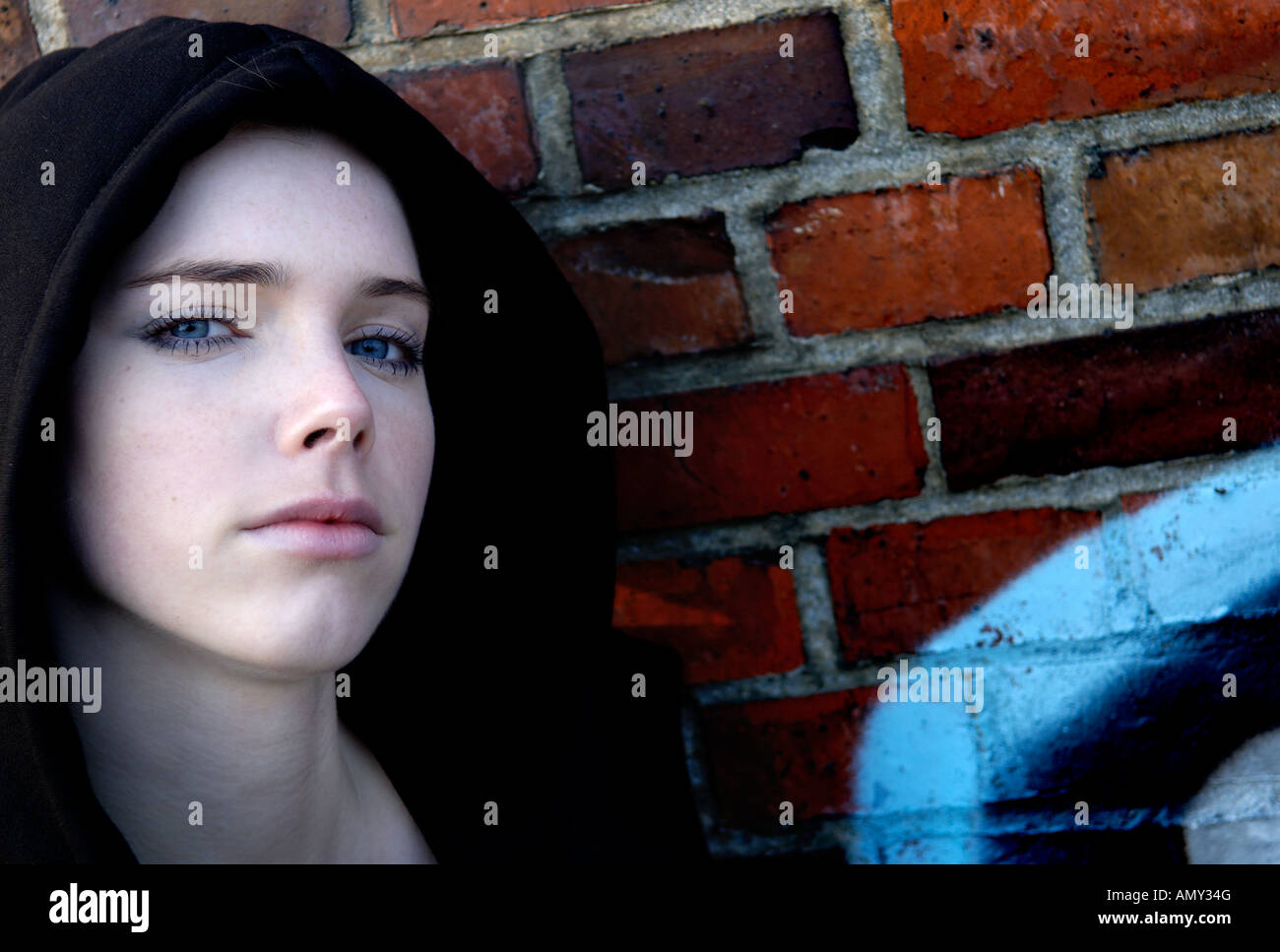 Portrait of young woman leaning against wall - Stock Image