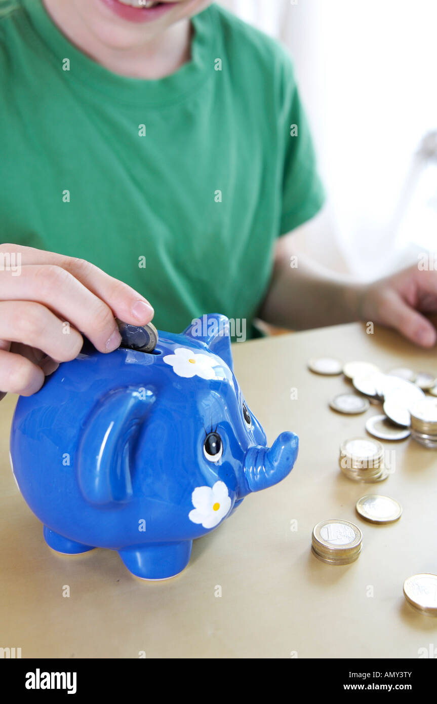 Close-up of boy inserting coin in piggybank - Stock Image