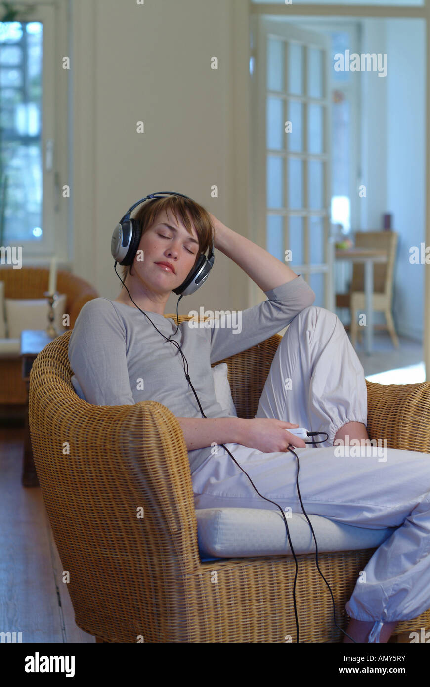 Young woman sitting in a basket-chair, listening to music - Stock Image