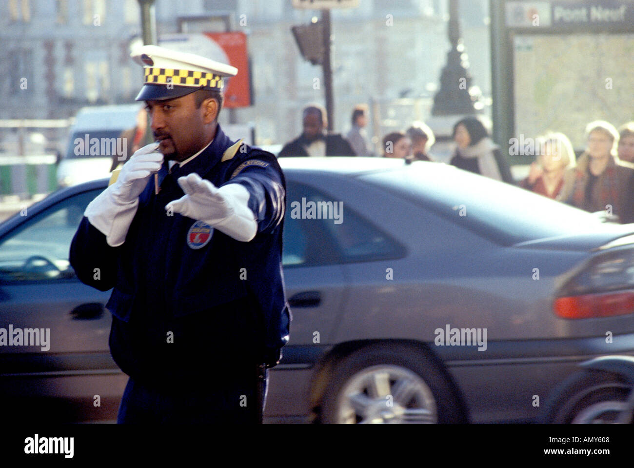 Paris traffic policement blowing whistle and signalling stop outside Pont Neuf Metro station Stock Photo