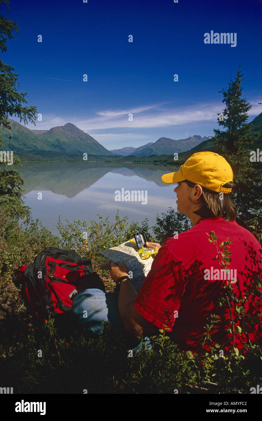 Hiker Reads Map Compass Trail Lake KP AK Summer - Stock Image