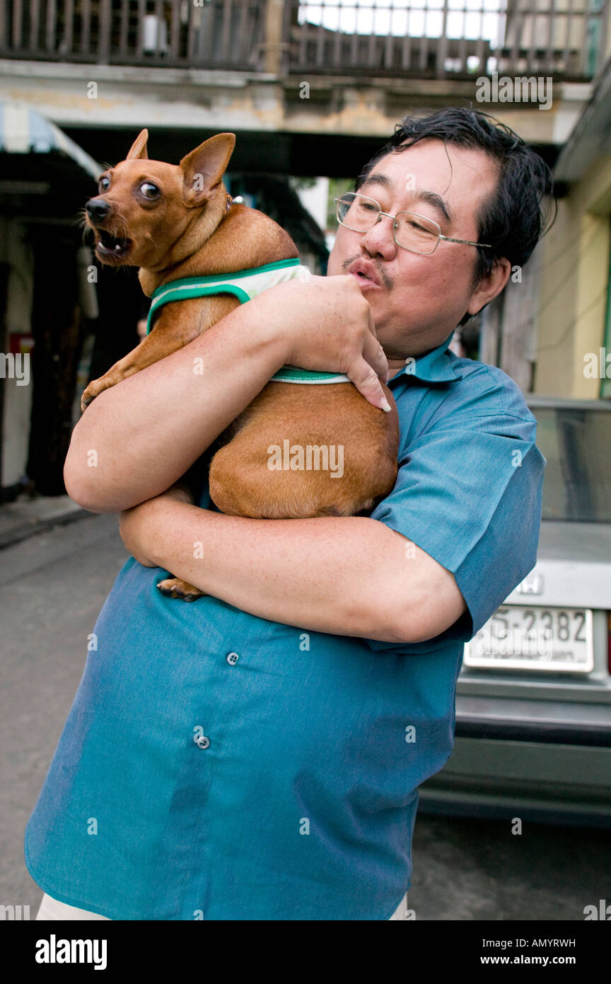 Man holding an angry dog in the Chinatown market area of Bangkok Thailand - Stock Image