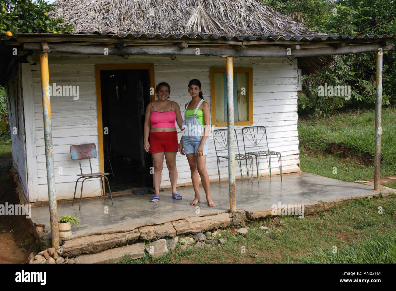 Women standing by their bohio or thatched house in Pinar Province, Cuba. - Stock Image