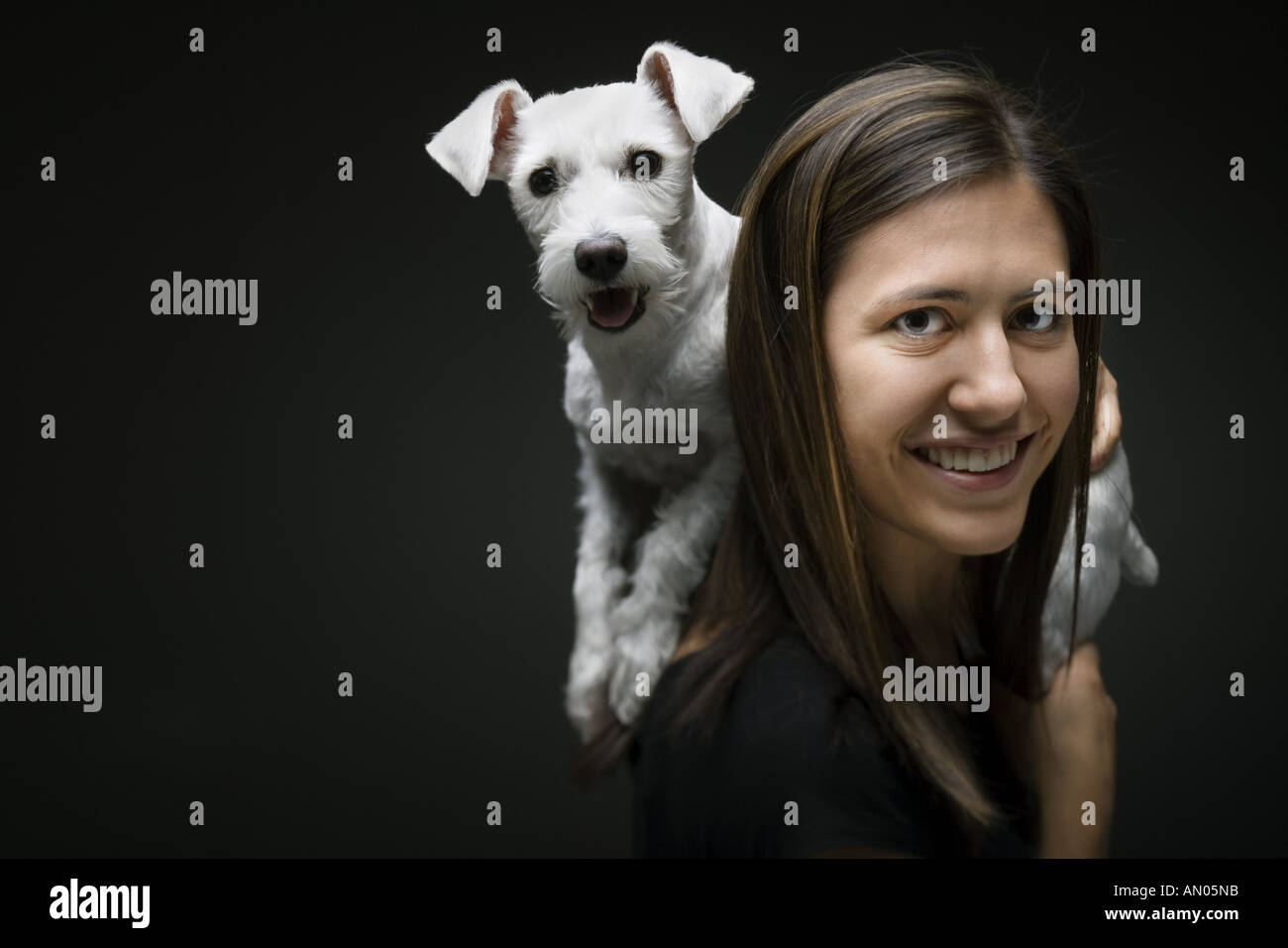 Portrait of a young woman carrying a dog on her shoulders and smiling - Stock Image