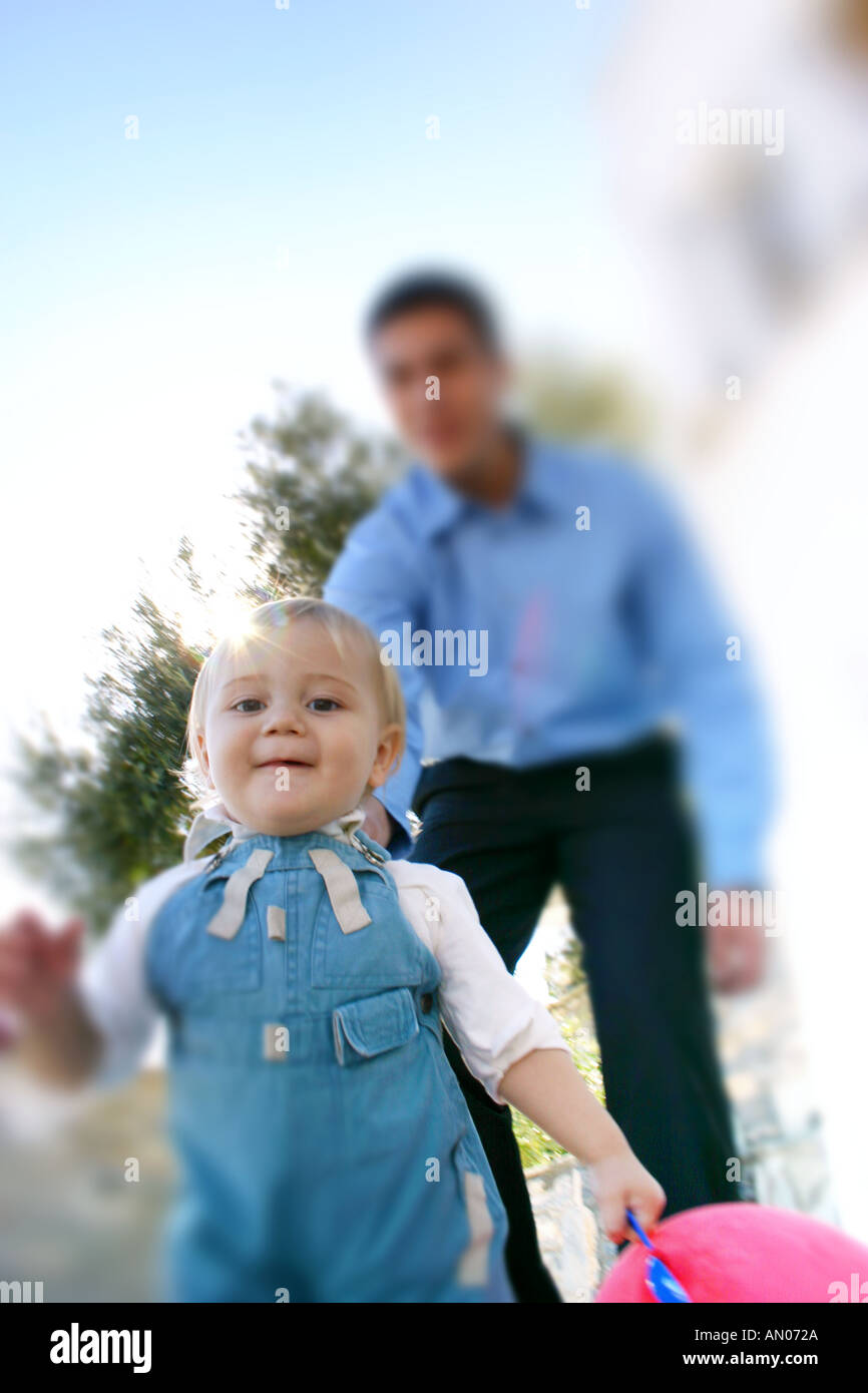 Little boy playing ''catch me if you can'' with adult man Stock Photo