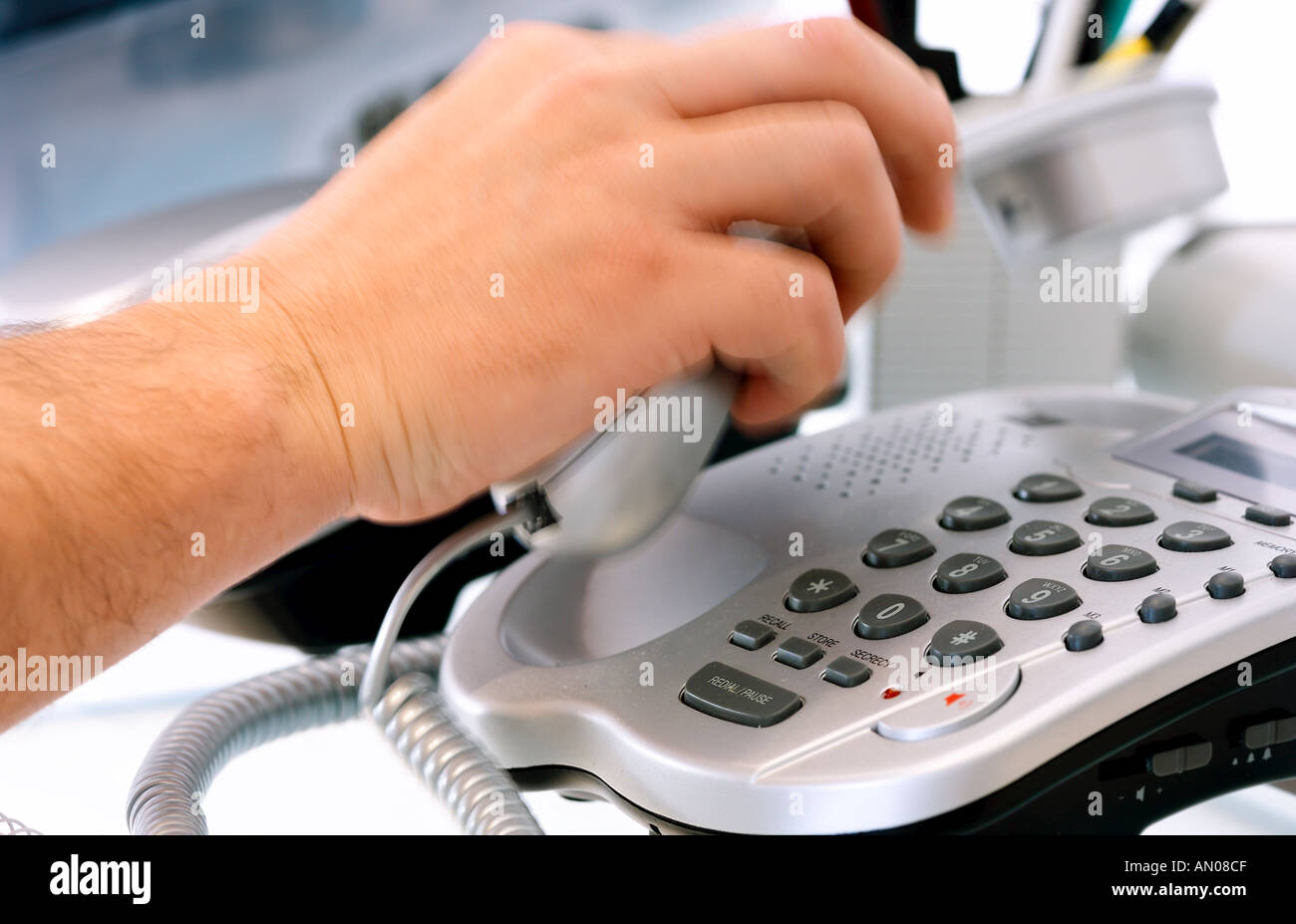 person answering a silver phone in a office - Stock Image